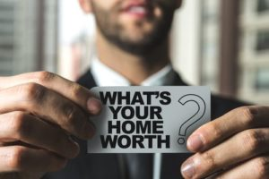"Bearded man in a suit holding a piece of paper that reads, ""What's Your Home Worth?"""