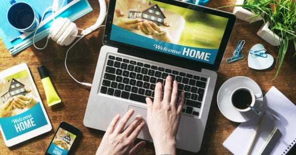 laptop computer shows person typing on keywboard and screen has a real estate agent website open