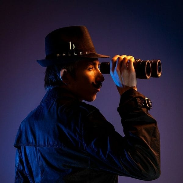 Man in dark coat with binoculars spying on the competition