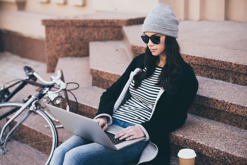 What is a Blog - Woman sits on step typing her blog post