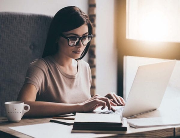 Woman is on her computer and is buying a domain name for her WordPress Blog