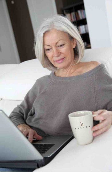 Woman is on her computer writing her blog for her business, coffee in hand