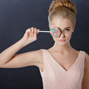 fashion model holding a lollipop over her right eye to represent image optimization