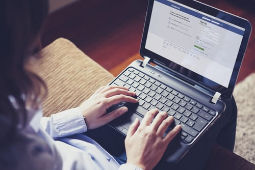 person on a laptop computer looking at a Facebook Business Page