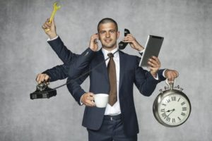 man in gray suit with brown tie and six arms holding gadgets to represent multitasking in lead nurturing