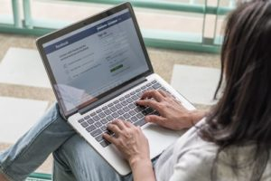 hands on a laptop using Facebook to create custom audiences