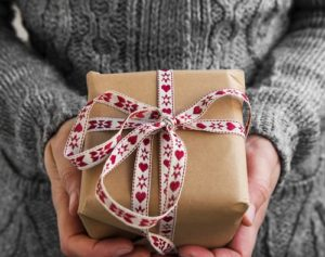 woman in gray sweater with a holiday gift wrapped in rustic paper