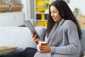 Woman in a gray sweater holding a red and white coffee mug reading a Real Estate Market Report on a tablet