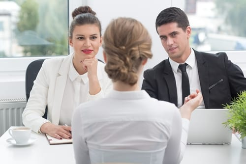 business professionals communicating at a table around a computer