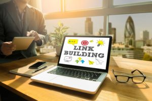 desk in a sunny office with a laptop displaying the words: Link Building