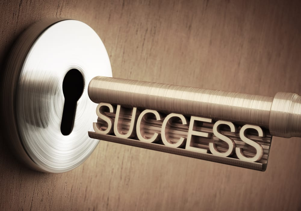 Key is intering a keyhole and the key has the word success spelled out