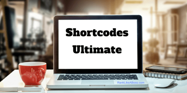 Computer screen reads Shortcodes ultimate, red coffee mug with Ballen Logo to left, pen on the table, keyword has banner reading ranklikeaboss.com
