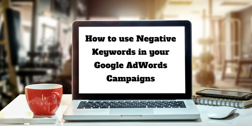 Computer screen on a table reads how to use negative keywords in your google Adwords Campaign, Coffee cup nearby