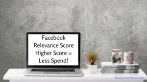 """Computer is on a table with a plant, books, money jar, coffee mug. Grey wall with a lot of blank space. Computer screen reads """"Facebook Relevance Score Higher Score = Less Spend!"""""""
