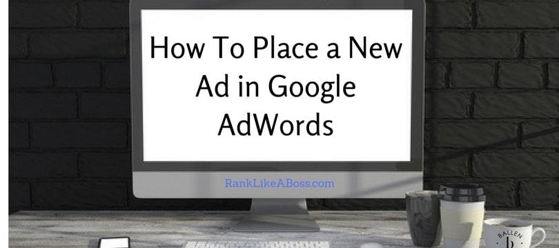 """Large computer is on a desk, wall behind it is dark. On the desk is a coffee mug, water glass, iphone. Computer reads """"how to place a new ad in google adwords"""""""