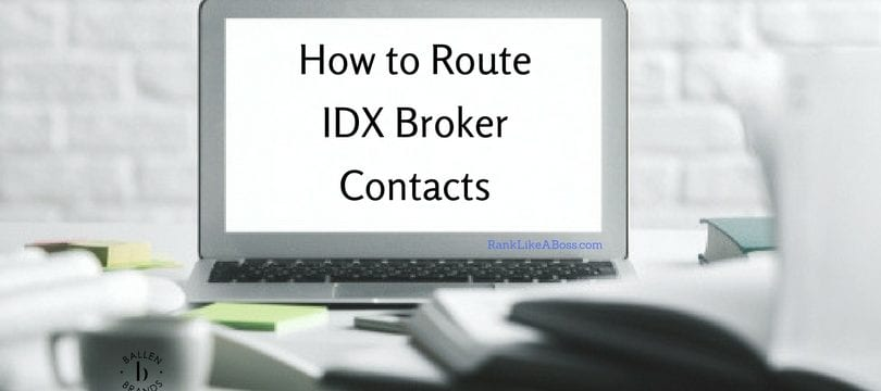 Computer screen is on a desk and there is white brick wall behind it. Computer screen reads how to route idx broker contacts