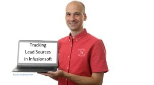 Man in red shirt with Ballen Brands logo is holding a computer that reads tracking lead sources in infusionsoft