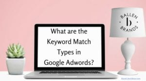 Computer is sitting on a desk, pink wall behind it, words on computer are large and read what are the keyword match types in google adwords