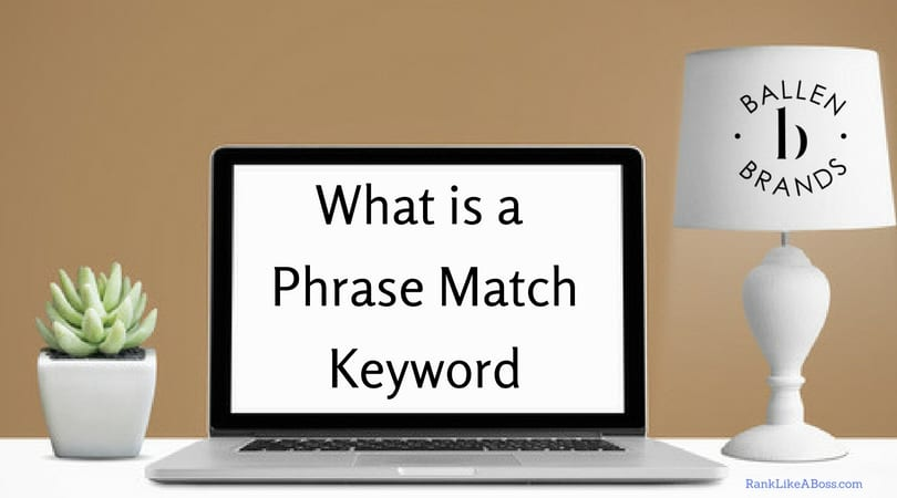 What is a phrase match keyword is written on a blank computer screen against a brown wall