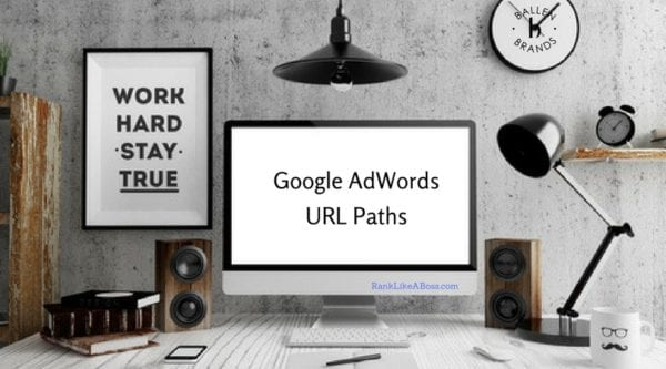 Google Adwords URL paths is spelled out on a computer screen on a desk with black lamp, sign that says work hard play, pen, mouse, phone