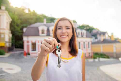 Young Real Estate Agent is holding up a pair of keys as if she sold her first house. She is standing in front of a beautiful large home