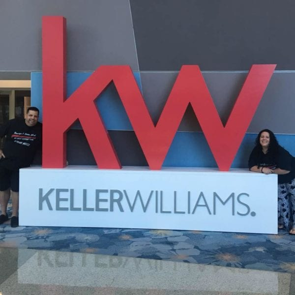 Keller Williams sign with Large Red KW and Elizabeth Mucci is standing on one side and her husband on the other