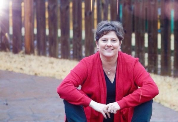Robin Mann, Real Estate Agent is sitting in front of a fence, smiling, wearing a red cardigan