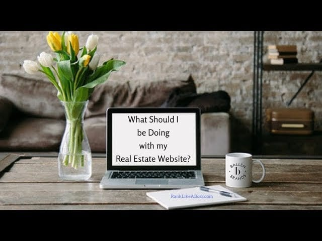 laptop computer is on a coffee table with a vase of flowers, coffee mug with Ballen Brands logo, and a pad and pen, letters on the screen spell out the words What Should I be doing with my real estate agent website