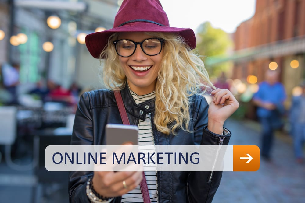Girl with a hat and moto jacket is holding a cell phone while walking down the street. She is smiling. There is a search bar showing on the image that has the letters that make the words online marketing