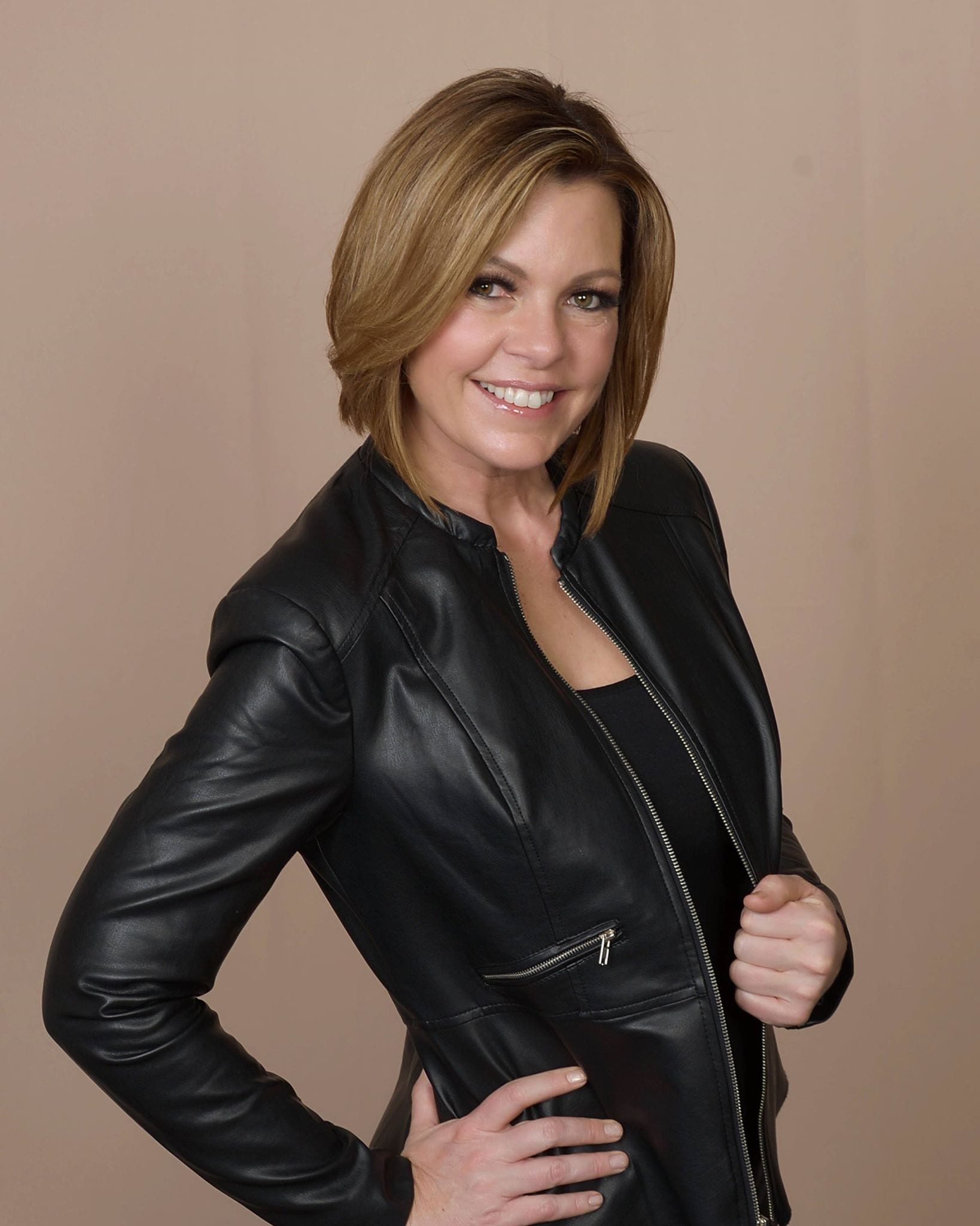 Lori Ballen is standing with a smile and holding on to her leather jacket