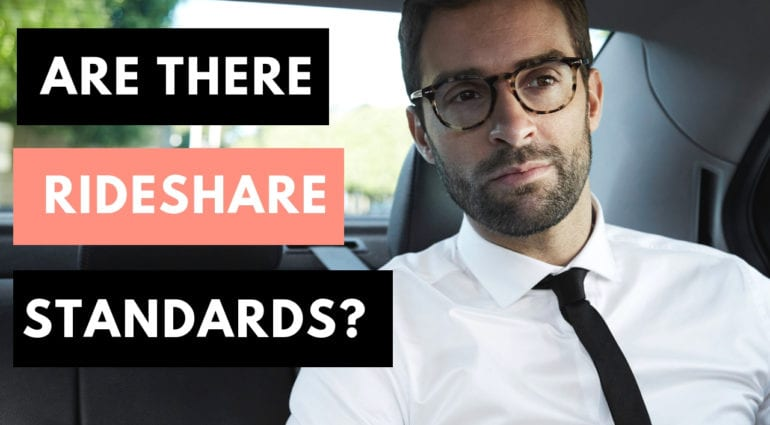 Man with glasses looks like he is in business attire with a white shirt and black tie. He is in the back of a car which could be a lyft or uber rideshare