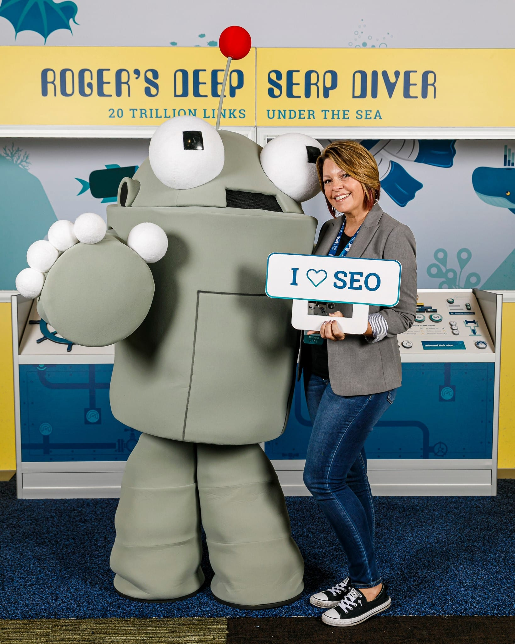 Lori Ballen Realtor, Digital Marketing Strategist, Affiliate Marketer, Speaker/Trainer stands next to Roger, the Moz Mascot. Lori was attending the Mozcon convention in Seattle and she is holding an I love SEO sign